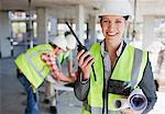 Femme d'affaires parlant talkie walkie sur chantier