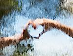Hands making heart-shape behind glass