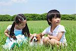 Fille et garçon jouant avec mascotte chien