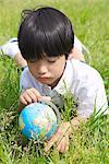 Boy Lying on Grass with Globe