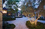 Haus außen bei Nacht mit einem Brunnen, eine Laterne und Bäumen, in dem mit Lichterketten beleuchtet ist