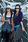 Jeunes filles de l'adolescence avec la planche à roulettes et pot de peinture en aérosol