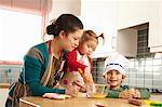 Mère cuisiner avec les enfants dans la cuisine