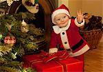 Un standing de santa baby à côté d'un cadeau
