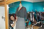 woman in shop window dressing mannequin