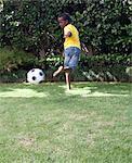Boy kicking soccer ball, Johannesburg, South Africa