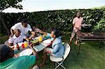 Gens assis à l'extérieur avec barbecue en arrière-plan, Johannesburg, Afrique du Sud