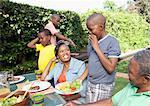 Mère souriant à fils à l'étranger ayant braai, Johannesburg, Afrique du Sud