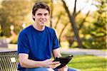 Man Sitting on Park Bench Holding iPad