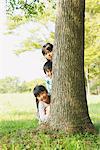 Enfants se cachent derrière le tronc d'arbre