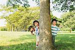 Children Hiding Behind Tree Trunk