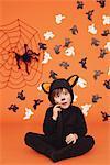 Junge im Cat-Kostüm für Halloween Orange Hintergrund sitzen
