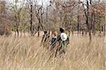 India, Madhya Pradesh, Satpura National Park. Young couple follow a park ranger through grass on a walking safari.