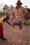 Kenya, District de Samburu. Une touriste tente de sauter aussi haut comme un guerrier Samburu, dans le lit de rivière asséchée de la Ewaso Nyiro.
