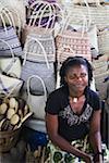 Woman vendor selling woven bags at market, Inhambane, Mozambique