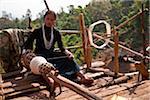 Myanmar, Burma, Keng Tung (Kyaing Tong). An Ann (Enn) lady spinning thread on the platform of her home, Paunglea village, Keng Tung.