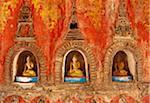 Myanmar, Burma, Nyaungshwe. A trio of small Buddhas set into the temple wall, Shwe Yaunghwe Kyaung monastery, near Inle Lake.