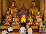 Myanmar, Birmanie, Rangoon, Rangoon. Adorateurs dévots prier devant des statues de Bouddha dorés, un avec un halo de rayonnant de lumière électrique, à la pagode Shwedagon de Rangoon.