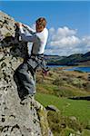 UK, North Wales, Snowdonia.  A man rock climbing on a large granite boulder near Snowdon.