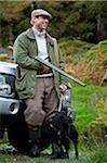 Pays de Galles, Snowdonia ; GILAR ferme. Un homme détend penchement contre son landrover alors qu'à la chasse.