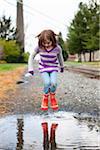 Jeune fille sautant dans les flaques