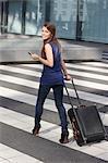 Femme avec valise et téléphone portable