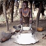 À l'ombre du soleil chaud, une femme de Karo broie du sorgho à l'aide de grosses pierres plates.Il est de coutume pour les femmes de la tribu lorsque dans leurs adolescents à faire un petit trou dans la chair sous leur lèvre inférieure dans laquelle ils ont mis un ornement, cette femme a utilisé un petit clou. Nombreux métaux lourds bracelets portent des mariés womenThe Karo sont une tribu vivant dans trois villages principaux le long de la basse o atteint