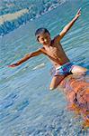 boy riding log in lake
