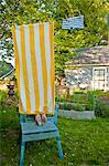 boy on garden chair under beach towel