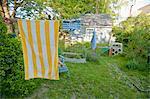 garçon sur chaise de jardin sous la serviette de plage