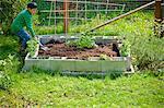boy tending small raised garden bed