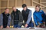 Quatre charpentiers discutant un dessin, Stockholm, Suède.
