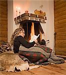 Une femme lisant un livre devant la cheminée, Suède.