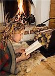 Une femme lisant en face de la cheminée, Suède.