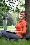 Eine Frau in einem Park mit einem Laptop, Schweden.