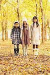 Three Girls Standing In Park in Autumn