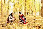 Jeunes filles jouant dans les feuilles de l'automne