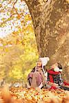 Girls Sitting And Enjoying Near Tree Trunk