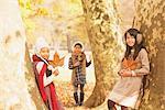 Filles appuyé contre l'arbre tenant la feuille d'érable