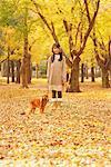 Fille avec un chien Pet dans le feuillage d'automne