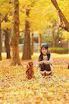 Fille accroupie avec mascotte chien dans le feuillage d'automne