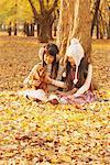 Filles tenant le chien dans les feuilles