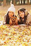 Filles préados couchée dans les feuilles avec chien