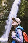 Young Woman Looking Up nahe Wasserfall amüsiert