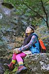 Junge Frau Wanderer sitzend auf einem Felsen, Blick nach oben