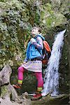 Jeune femme randonneur près de cascade a amusé