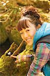 Jeune femme pointant vers une culture d'espèces végétales en bois