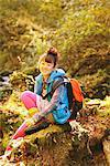 Jeune femme randonneur assis sur bois recouverts de mousse