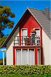 Une figurine de père miniature tenant sa fille sur le balcon d'une maison de poupée