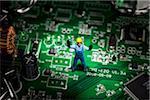 Un ouvrier du bâtiment miniature figurine debout sur une carte mère de l'ordinateur